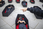 Women laying in coffins representing women killed in domestic violence during an event for upcoming International Women's Day in front of Tel Aviv's district court, Israel, Sunday, March 7, 2021. (AP Photo/Ariel Schalit)