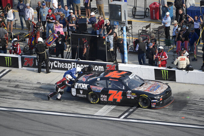 Crew members push Mike Harmon (74) through a pit stall during a NASCAR Xfinity Series auto race at Daytona International Speedway Saturday, Feb. 16, 2019, in Daytona Beach, Fla. (AP Photo/Phelan M. Ebenhack)