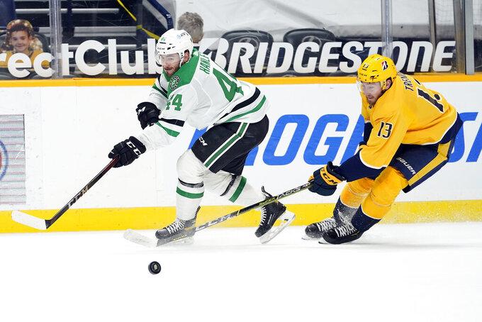 Dallas Stars defenseman Joel Hanley (44) and Nashville Predators center Yakov Trenin (13) battle for the puck in the second period of an NHL hockey game Sunday, April 11, 2021, in Nashville, Tenn. (AP Photo/Mark Humphrey)