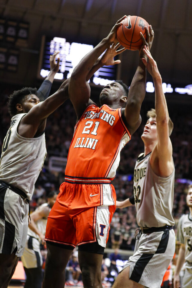 Illinois center Kofi Cockburn (21) shoots between Purdue forward Trevion Williams (50) and center Matt Haarms (32) during the first half of an NCAA college basketball game in West Lafayette, Ind., Tuesday, Jan. 21, 2020. (AP Photo/Michael Conroy)