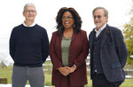 FILE - This March 25, 2019 file photo shows Apple CEO Tim Cook, from left, Oprah Winfrey and Steven Spielberg outside the Steve Jobs Theater during an event to announce new Apple products in Cupertino, Calif. Apple TV Plus launched Nov. 1 with Winfrey and Spielberg among its first wave of producers, and was quickly followed by Disney Plus. (AP Photo/Tony Avelar, File)