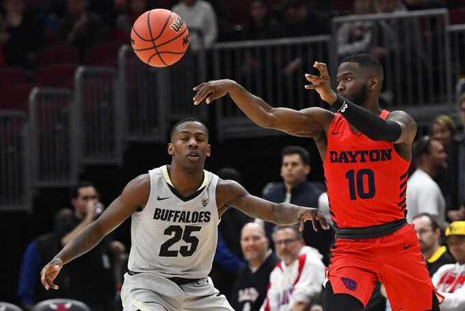 Dayton guard Jalen Crutcher (10) passes away from Colorado guard McKinley Wright IV (25) in the first half of an NCAA college basketball game, Saturday, Dec. 21, 2019, in Chicago. (AP Photo/Matt Marton)