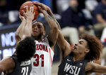 Arizona guard Terrell Brown Jr. (31) gets squeezed into a miss by Washington State center Dishon Jackson (21), left, and guard Isaac Bonton during the first half of an NCAA college basketball game Thursday, Feb. 25, 2021, in Tucson, Ariz. (Kelly Presnell/Arizona Daily Star via AP)