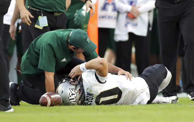 A trainer from South Florida attends to Central Florida quarterback McKenzie Milton after he went down with an apparent knee injury during the first half of an NCAA college football game Friday, Nov. 23, 2018, in Tampa, Fla. (AP Photo/Mike Carlson)