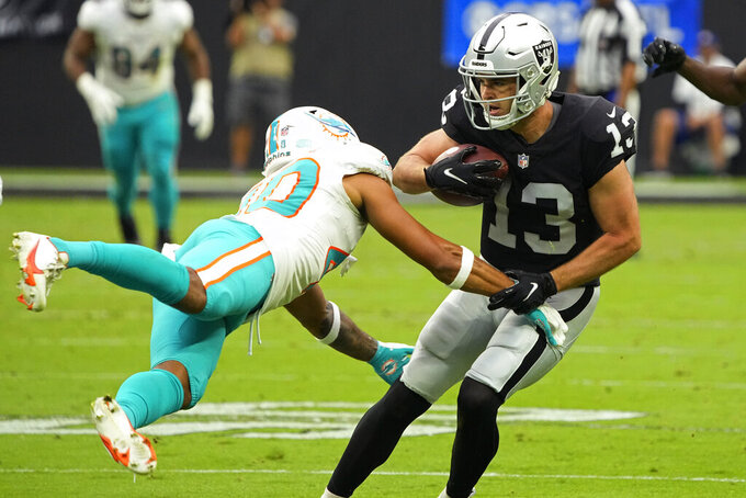 Miami Dolphins defensive back Nik Needham (40) attempts to tackle Las Vegas Raiders wide receiver Hunter Renfrow (13) during the first half of an NFL football game, Sunday, Sept. 26, 2021, in Las Vegas. (AP Photo/Rick Scuteri)