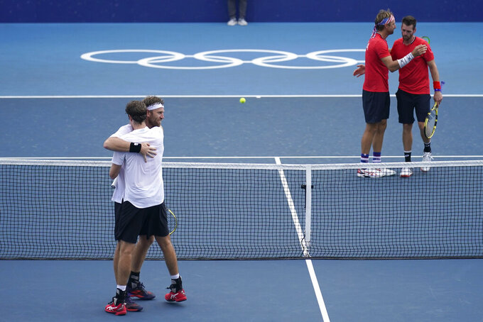 The New Zealand doubles team of Michael Venus, left, and Marcus Daniell, second from left, react after defeating the team from the United States, Tennys Sandgren, second from right, and Austin Krajicek, during the men's doubles bronze medal match of the tennis competition at the 2020 Summer Olympics, Friday, July 30, 2021, in Tokyo, Japan. (AP Photo/Seth Wenig)