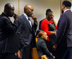 Victim Botham Jean's mother, Allison Jean, second from right, wipes tears from her eyes after her son Brandt Jean hugged defendant Amber Guyger following the impact segment during court, Wednesday, Oct. 2, 2019, in Dallas. Fired Dallas Police Officer Guyger, who said she mistook neighbor Botham Jean's apartment for her own and fatally shot him in his living room, was sentenced to a decade in prison. (Tom Fox/The Dallas Morning News via AP, Pool)