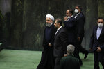 Iranian President Hassan Rouhani, left, arrives for the inauguration of the new parliament, in Tehran, Iran, Wednesday, May, 27, 2020. Iran has convened its newly elected parliament, dominated by conservative lawmakers and under strict social distancing regulations, as the country struggles to curb the spread of coronavirus that has hit the nation hard. Iran is grappling with one of the deadliest outbreaks in the Middle East. (AP Photo/Vahid Salemi)