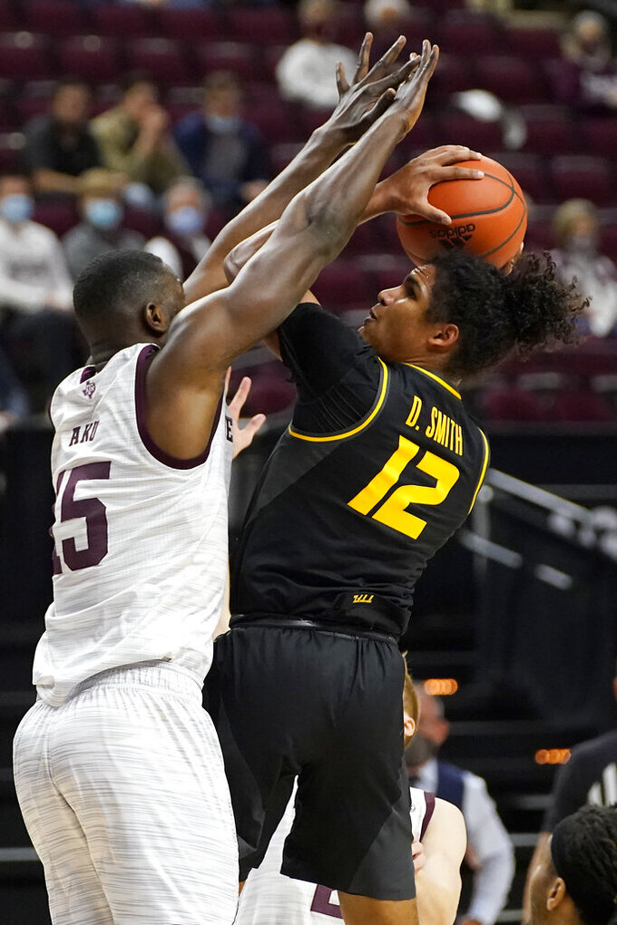 Missouri guard Dru Smith (12) drives the lane against Texas A&M forward Jonathan Aku (15) during the first half of an NCAA college basketball game Saturday, Jan. 16, 2021, in College Station, Texas. (AP Photo/Sam Craft)