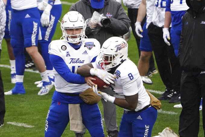 Tulsa quarterback Zach Smith (11) hands the ball to running back Deneric Prince (8) during warmups before they play Mississippi State in the Armed Forces Bowl NCAA college football game Thursday, Dec. 31, 2020, in Fort Worth, Texas. (AP Photo/Jim Cowsert)