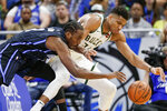 Orlando Magic's Al-Farouq Aminu, left, tries to steal the ball from Milwaukee Bucks' Giannis Antetokounmpo during the first half of an NBA basketball game Friday, Nov. 1, 2019, in Orlando, Fla. (AP Photo/John Raoux)