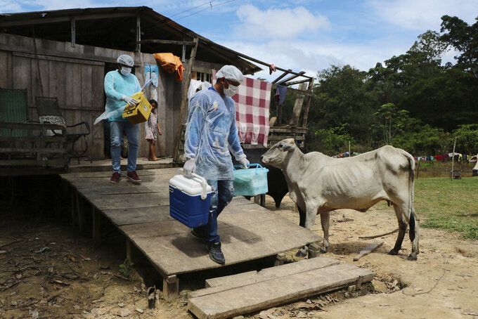 Health workers Diego Feitosa Ferreira, 28, right, and Clemilton Lopes de Oliveira, 41, leave a home after a resident denied to be vaccinated against the new coronavirus, in the Capacini community, along the Purus river, in the Labrea municipality, Amazonas state, Brazil, Friday, Feb. 12, 2021. Getting the vaccine to the world's farthest corners means delivering it by boat to Maine's islands, traveling by snowmobile to villages in Alaska and navigating complex waterways in Brazil's Amazon. (AP Photo/Edmar Barros)