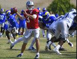 Dallas Cowboys quarterback Garrett Gilbert throws a pass against Los Angeles Rams defenders during an NFL football practice on Saturday, Aug 7, 2021, in Oxnard, Calif. (AP Photo/John McCoy)