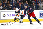 Edmonton Oilers' Kris Russell, left, and Columbus Blue Jackets' Oliver Bjorkstrand, of Denmark, chase a loose puck during the second period of an NHL hockey game Wednesday, Oct. 30, 2019, in Columbus, Ohio. (AP Photo/Jay LaPrete)