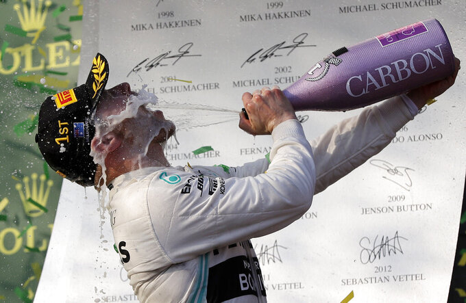 Mercedes driver Valtteri Bottas of Finland sprays himself with champagne after winning the Australian Formula 1 Grand Prix in Melbourne, Australia, Sunday, March 17, 2019. Bottas won ahead of teammate Lewis Hamilton of Britain while Red Bull driver Max Verstappen of the Netherlands placed third.(AP Photo/Rick Rycroft)