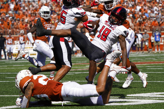 Texas Tech wide receiver Myles Price (18) is upended by Texas defensive back Christian Tschauner (26) during the first half of an NCAA college football game on Saturday, Sept. 25, 2021, in Austin, Texas. (AP Photo/Chuck Burton)