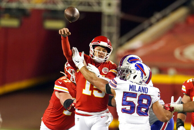 Kansas City Chiefs quarterback Patrick Mahomes (15) throws a pass as he is pressured by Buffalo Bills linebacker Matt Milano (58) during the first half of the AFC championship NFL football game, Sunday, Jan. 24, 2021, in Kansas City, Mo. (AP Photo/Charlie Riedel)