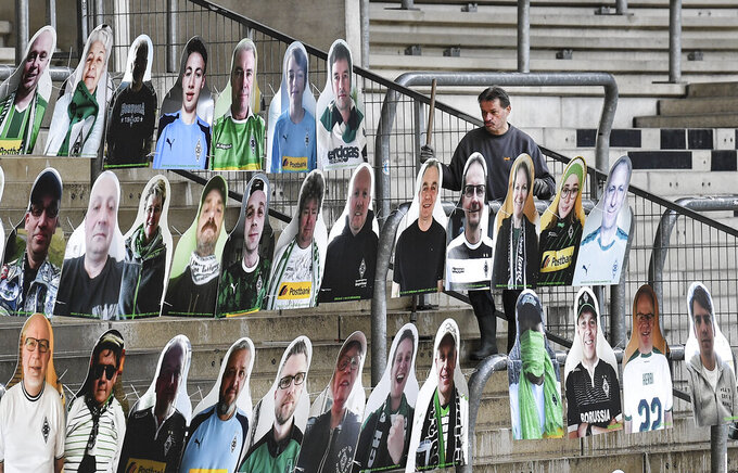 Portraits of fans of German Bundesliga soccer club Borussia Moenchengladbach are set on the supporters tribune in the stadium in Moenchengladbach, Germany, Thursday, April 16, 2020. All major events in Germany are suspended due to the coronavirus outbreak until the end of August, the German Bundesliga suspended all matches until April 30, 2020. (AP Photo/Martin Meissner)