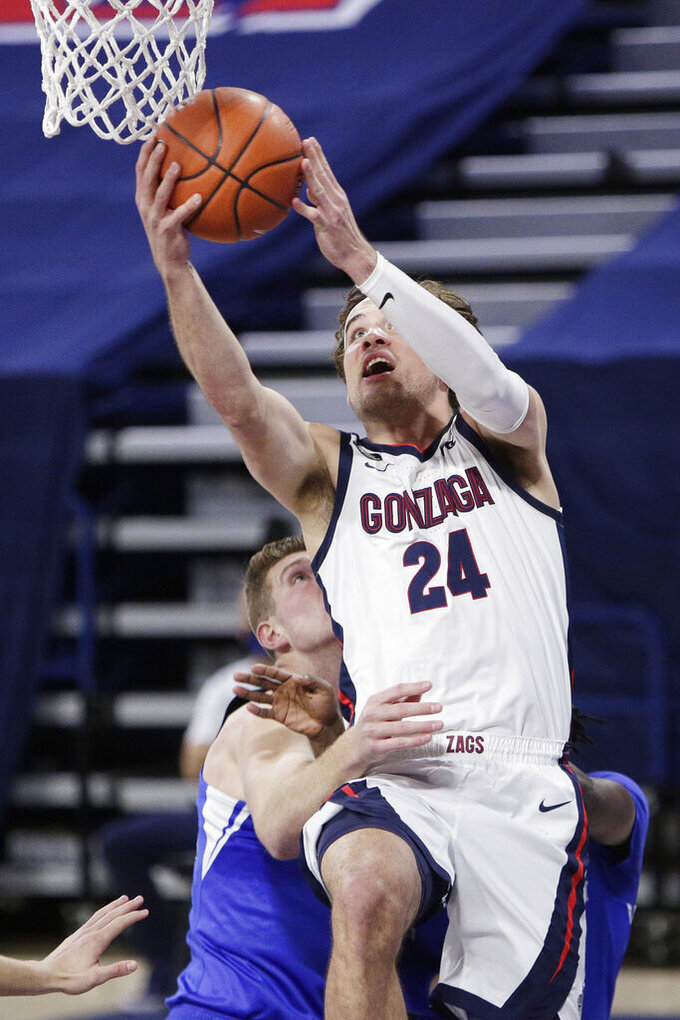 Gonzaga forward Corey Kispert, right, shoots over BYU forward Kolby Lee during the first half of an NCAA college basketball game in Spokane, Wash., Thursday, Jan. 7, 2021. (AP Photo/Young Kwak)