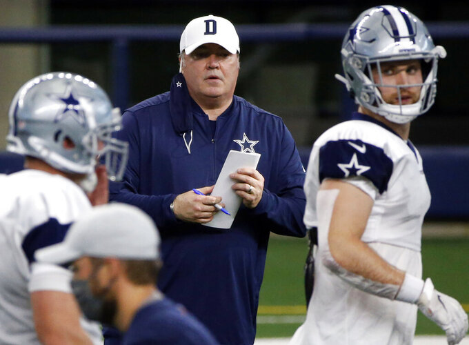 """FILE - In this Aug. 30, 2020, file photo, Dallas Cowboys head coach Mike McCarthy watches practice during an NFL football training camp in Arlington, Texas. The coronavirus pandemic could lead to pandemonium on offensive lines throughout the NFL. """"As you watch the linemen in particular, their pad level starts out high, their fits on their blocks are not as tight, the timing of how the combination block occurs going onto the second level's inconsistent,"""" says new Cowboys coach McCarthy. (AP Photo/Michael Ainsworth, File)"""