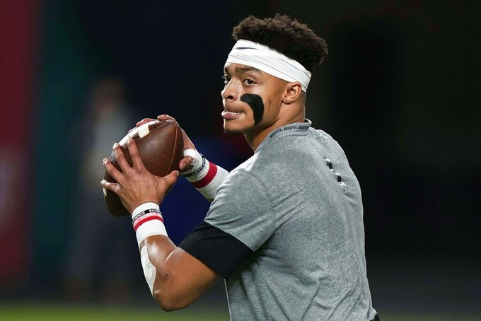 Ohio State quarterback Justin Fields warms up before an NCAA College Football Playoff national championship game against Alabama Monday, Jan. 11, 2021, in Miami Gardens, Fla. (AP Photo/Lynne Sladky)