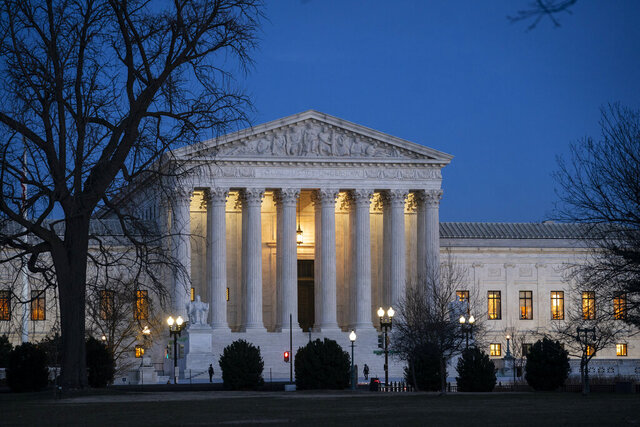 "FILE - In this Jan. 22, 2020, file photo, Night falls on the Supreme Court in Washington. The Supreme Court is about to tell President Donald Trump whether he has more power to use a favorite phrase: ""You're fired."" A case being argued at the high court Tuesday could threaten the structure of agencies that form an enormous swath of the federal government. It has to do with whether Trump, and future presidents, can fire the heads of independent agencies for any reason.  (AP Photo/J. Scott Applewhite, File)"