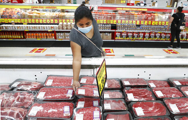 FILE - In this April 29, 2020 file photo, amid concerns of the spread of COVID-19, a shopper wears a mask as she looks over meat products at a grocery store in Dallas.  U.S. wholesale prices rose 0.3% in December led by a the biggest jump in energy costs since June. The Labor Department reported Friday, Jan. 15, 2021 that the gain in its producer price index, which measures inflation pressures before they reach consumers, followed a modest 0.1% gain in November and matched the 0.3% rise in October.(AP Photo/LM Otero, File)