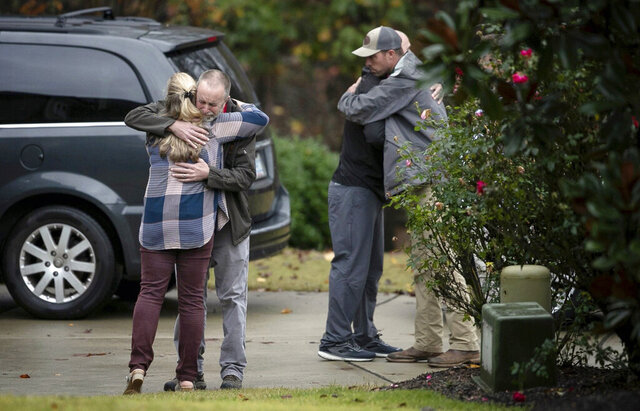 Neighbors console each other on Lord Granville Way in Rolesville, N.C., on Thursday, Nov. 12, 2020, after a neighborhood child drowned in a nearby flooded creek following heavy rains, according to The News & Observer. (Robert Willett/The News & Observer via AP)