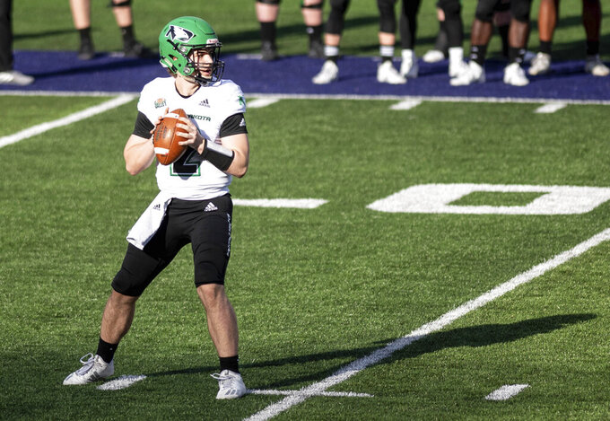 North Dakota quarterback Tommy Schuster (2) looks for an open receiver during the first half of a quarterfinal game against James Madison in the NCAA FCS football playoffs in Harrisonburg, Va., Sunday, May 2, 2021. (Daniel Lin/Daily News-Record via AP)
