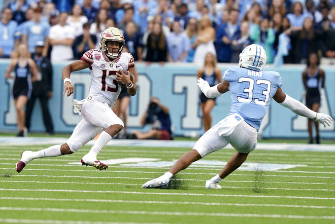 Florida State quarterback Jordan Travis (13) runs the ball against North Carolina linebacker Cedric Gray (33) during the first half of an NCAA college football game in Chapel Hill, N.C., Saturday, Oct. 9, 2021. (AP Photo/Gerry Broome)