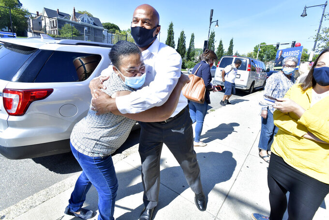 Mayoral Candidate John Barros greets supporter Arlette Santos of Boston outside a polling place in the Dorchester neighborhood of Boston on Tuesday, Sept. 14, 2021 in a preliminary mayoral election that will select two top contenders from a field of five candidates all of whom are people of color, four of them women. (AP Photo/Josh Reynolds)