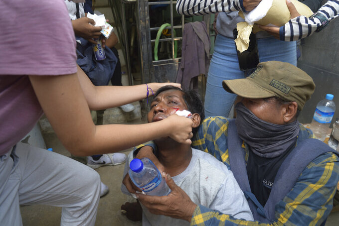 Anti-coup protesters attend to an injured rallyist during a demonstration in Yangon, Myanmar on Tuesday March 30, 2021. Thailand's Prime Minister Prayuth Chan-ocha denied Tuesday that his country's security forces have sent villagers back to Myanmar who fled from military airstrikes and said his government is ready to shelter anyone who is escaping fighting. (AP Photo)