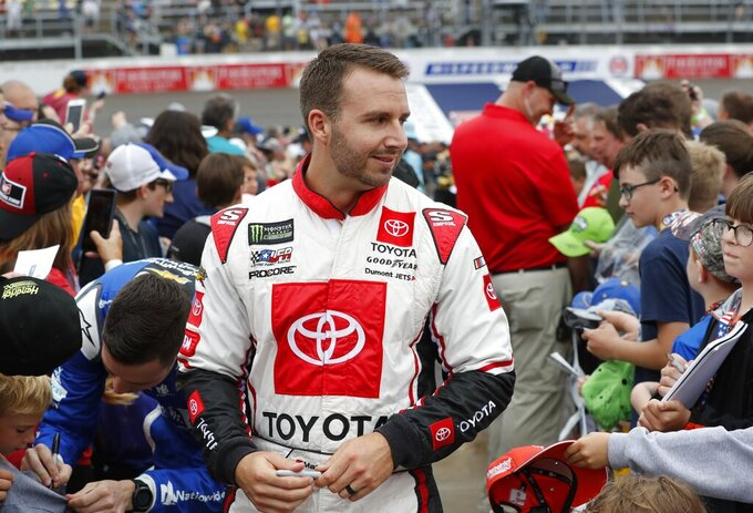 Matt DiBenedetto signs autographs before the NASCAR cup series auto race at Michigan International Speedway, Sunday, June 9, 2019, in Brooklyn, Mich. (AP Photo/Carlos Osorio)