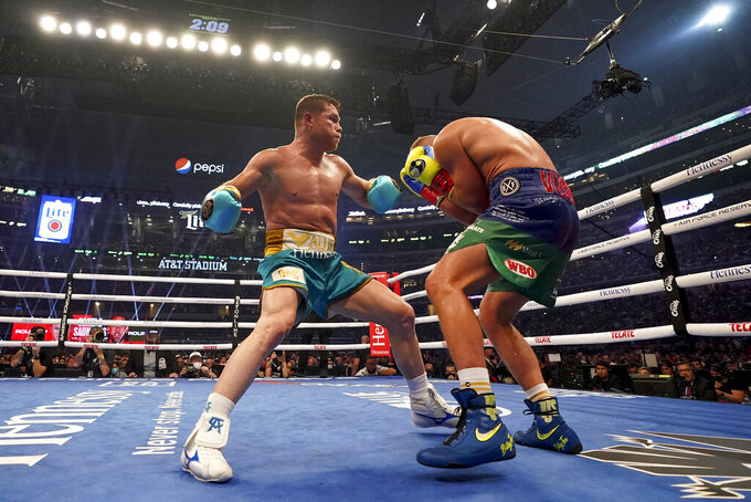 Canelo Alvarez, left, exchanges punches with Billy Joe Saunders during a unified super middleweight world championship boxing match, Saturday, May 8, 2021, in Arlington, Texas.(AP Photo/Jeffrey McWhorter)