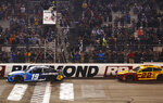 Martin Truex Jr. (19) crosses the finish line in front of Joey Logano (22) to win the NASCAR Cup Series auto race at Richmond Raceway in Richmond, Va., Saturday, April 13, 2019. (AP Photo/Steve Helber)