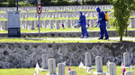 Quarantine officials disinfect as a precaution against the new coronavirus at the National Cemetery in Seoul, South Korea, Monday, June 1, 2020. South Korea is reporting a steady rise in cases around the capital as officials push to require entertainment venues to register their customers with smartphone QR codes so they could be easily located when needed. (Kim In-chul/Yonhap via AP)