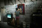 Adriana Rodriguez looks into a mirror as she applies mascara in a room she shares with her three sons and another family of seven, in a building occupied by squatters, in Caracas, Venezuela, Monday, May 6, 2019. In the fourth month of their standoff, Nicolas Maduro and opposition leader Juan Guaidó are unable to deliver a knock-out blow as Venezuela spirals deeper into neglect, isolation and desperation. (AP Photo/Rodrigo Abd)