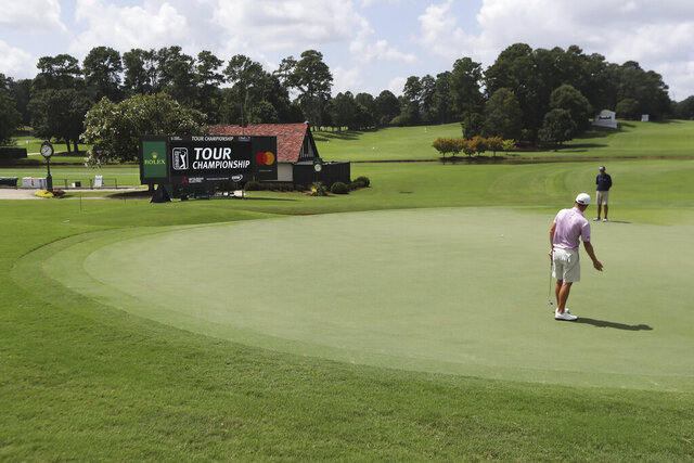 Justin Thomas and his instructor are the only ones around to react to his putt on the 18th green during his practice round for the season-ending Tour Championship at East Lake Golf Club on Wednesday, Sept. 2, 2020, in Atlanta. (Curtis Compton/Atlanta Journal-Constitution via AP)