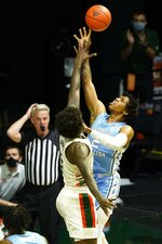 North Carolina guard Caleb Love (2) aims for a basket as Miami center Nysier Brooks (3) defends during the first half of an NCAA college basketball game, Tuesday, Jan. 5, 2021, in Coral Gables, Fla.(AP Photo/Marta Lavandier)