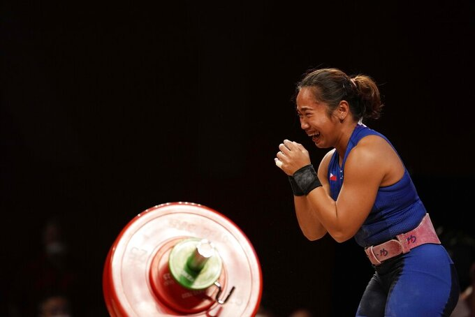 Hidilyn Diaz of Philippines celebrates as she sets the new world record and won the gold medal in the women's 55kg weightlifting event, at the 2020 Summer Olympics, Monday, July 26, 2021, in Tokyo, Japan. (AP Photo/Luca Bruno)