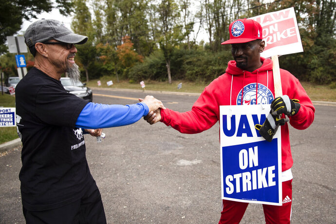 Picketing United Auto Workers Richard Rivera, left, and Will Myatt react to news of a tentative contract agreement with General Motors, in Langhorne, Pa., Wednesday, Oct. 16, 2019. Bargainers for General Motors and the United Auto Workers reached a tentative contract deal on Wednesday that could end a monthlong strike that brought the company's U.S. factories to a standstill. (AP Photo/Matt Rourke)