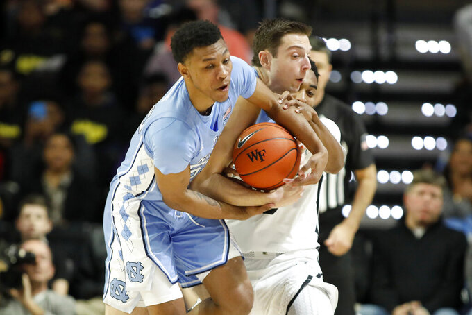 North Carolina's guard Christian Keeling (55) and Justin Pierce (32) work to keep the rebound against Wake Forest's Brandon Childress (0) in the first half of an NCAA college basketball game Tuesday, Feb. 11, 2020 in Winston-Salem, N.C. (AP Photo/Lynn Hey)