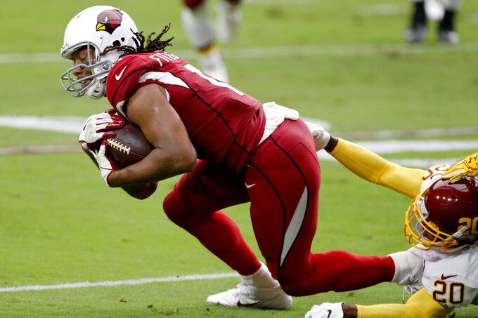 Arizona Cardinals wide receiver Larry Fitzgerald (11) is tackled by Washington Football Team cornerback Jimmy Moreland (20) during the first half of an NFL football game, Sunday, Sept. 20, 2020, in Glendale, Ariz. (AP Photo/Darryl Webb)