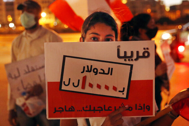 An anti-government protester holds a placard in Arabic that reads