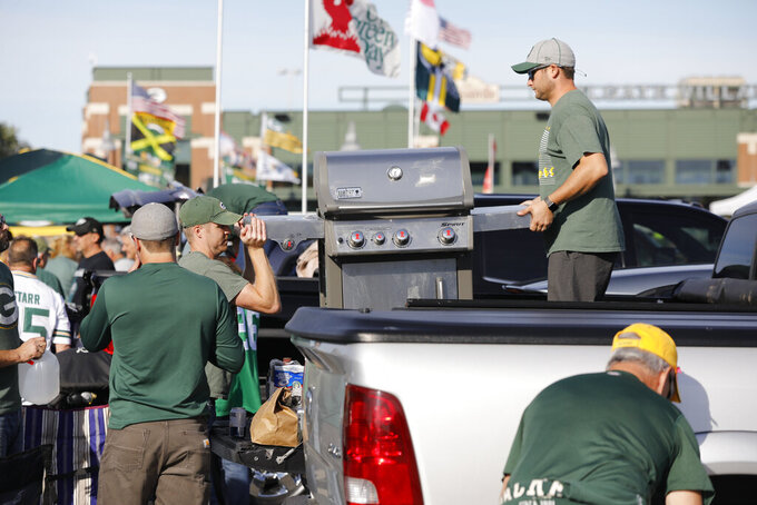 Fans unload a grill in preparation to tailgate outside Lambeau Field before an NFL football game between the Green Bay Packers and the Philadelphia Eagles, Thursday, Sept. 26, 2019, in Green Bay, Wis. (AP Photo/Mike Roemer)