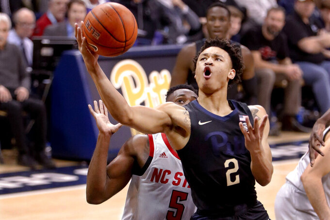 Pittsburgh's Trey McGowens (2) shoots as North Carolina State's Eric Lockett defends during the first half of an NCAA college basketball game, Saturday, Feb. 9, 2019, in Pittsburgh. (AP Photo/Keith Srakocic)