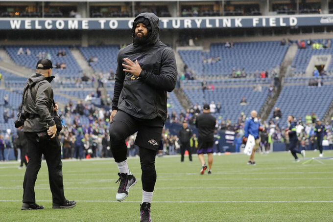 Baltimore Ravens free safety Earl Thomas, center, warms up before an NFL football game against his former team, the Seattle Seahawks, Sunday, Oct. 20, 2019, in Seattle. (AP Photo/Elaine Thompson)