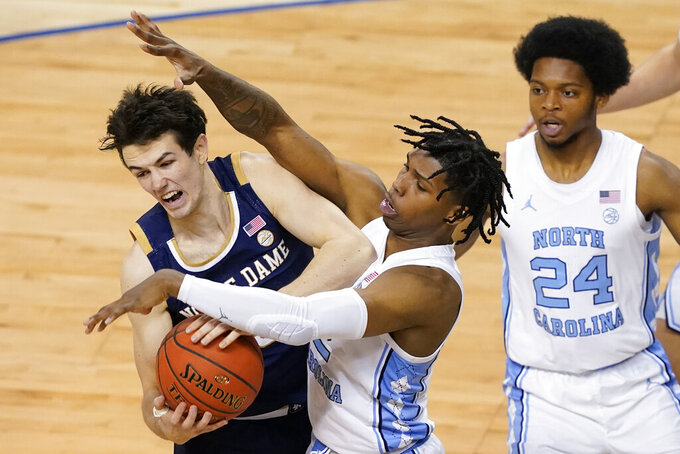 Notre Dame guard Cormac Ryan (5) tries to secure the ball as North Carolina guard Caleb Love, center, defends as North Carolina guard Kerwin Walton (24) closes in during the second half of an NCAA college basketball game in the second round of the Atlantic Coast Conference tournament in Greensboro, N.C., Wednesday, March 10, 2021. (AP Photo/Gerry Broome)