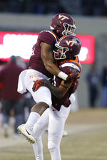 Virginia Tech wide receiver Tre Turner, right, celebrates a touchdown with teammate Eli Adams, left, during the first half of an NCAA college football game in Blacksburg, Va., Friday, Nov. 23, 2018. (AP Photo/Steve Helber)