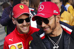 Ferrari driver Sebastian Vettel of Germany, left, chats with Mercedes driver Lewis Hamilton of Britain after attending an autograph session at the Shanghai International Circuit ahead of the Chinese Formula One Grand Prix in Shanghai, China, Thursday, April 11, 2019. (AP Photo/Andy Wong)